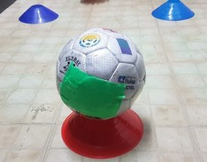 Soccer ball with target on side for visual and tactile assistance